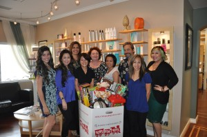 Pictured is the salon staff behind a full box of toys for the Marine Corps Reserves Toys for Tots Program.